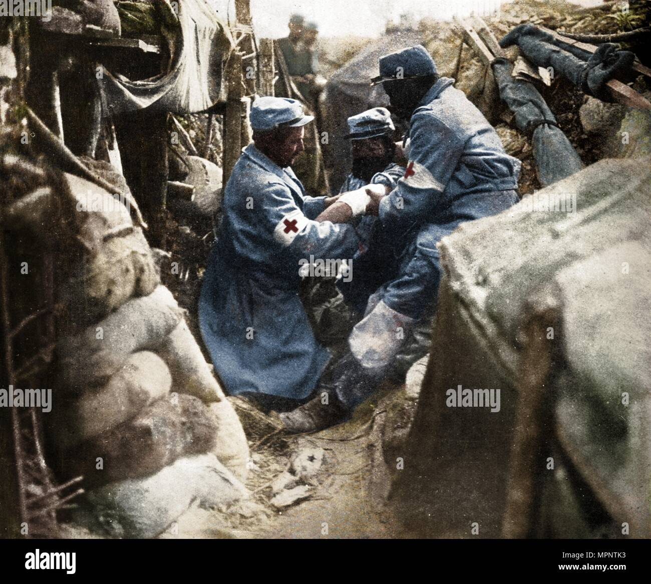 'First aid to a wounded man in one of the French trenches', 1915. Artist: Unknown. - Stock Image