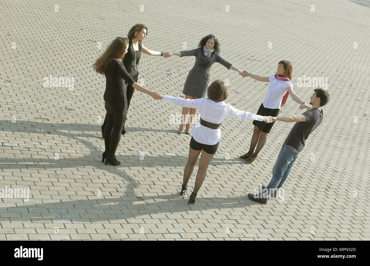 friendly group of students taking each other's hands. - Stock Image