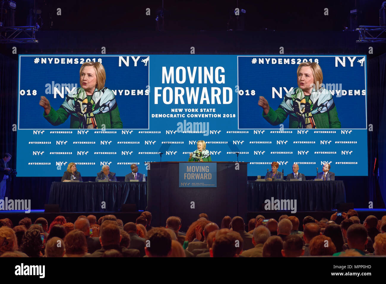 Long Island, USA. 23rd May, 2018. HILLARY CLINTON  delivers Keynote Address during Day 1 of New York State Democratic Convention, held at Hofstra University on Long Island. Clinton, the former First Lady and NYS Senator, endorsed the re-election of Gov. A. Cuomo for a third term, and mentioned how Hofstra was the site of her first 2016 debate with Trump. NYS Democratic Leaders on stage include CHRISTINE QUINN, Exec. Committee Chair, sitting to right of Clinton. Credit: Ann E Parry/Alamy Live News Stock Photo