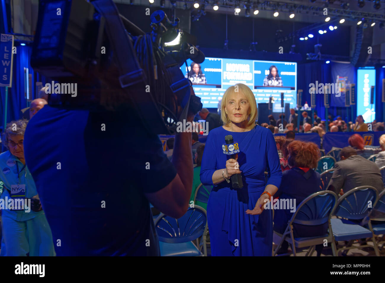 Long Island, USA. 23rd May, 2018. MARCIA KRAMER, WLNY 10/55 Political Reporter, tapes news segment with audience and stage in background during Day 1 of New York State Democratic Convention, held at Hofstra University on Long Island. Credit: Ann E Parry/Alamy Live News Stock Photo