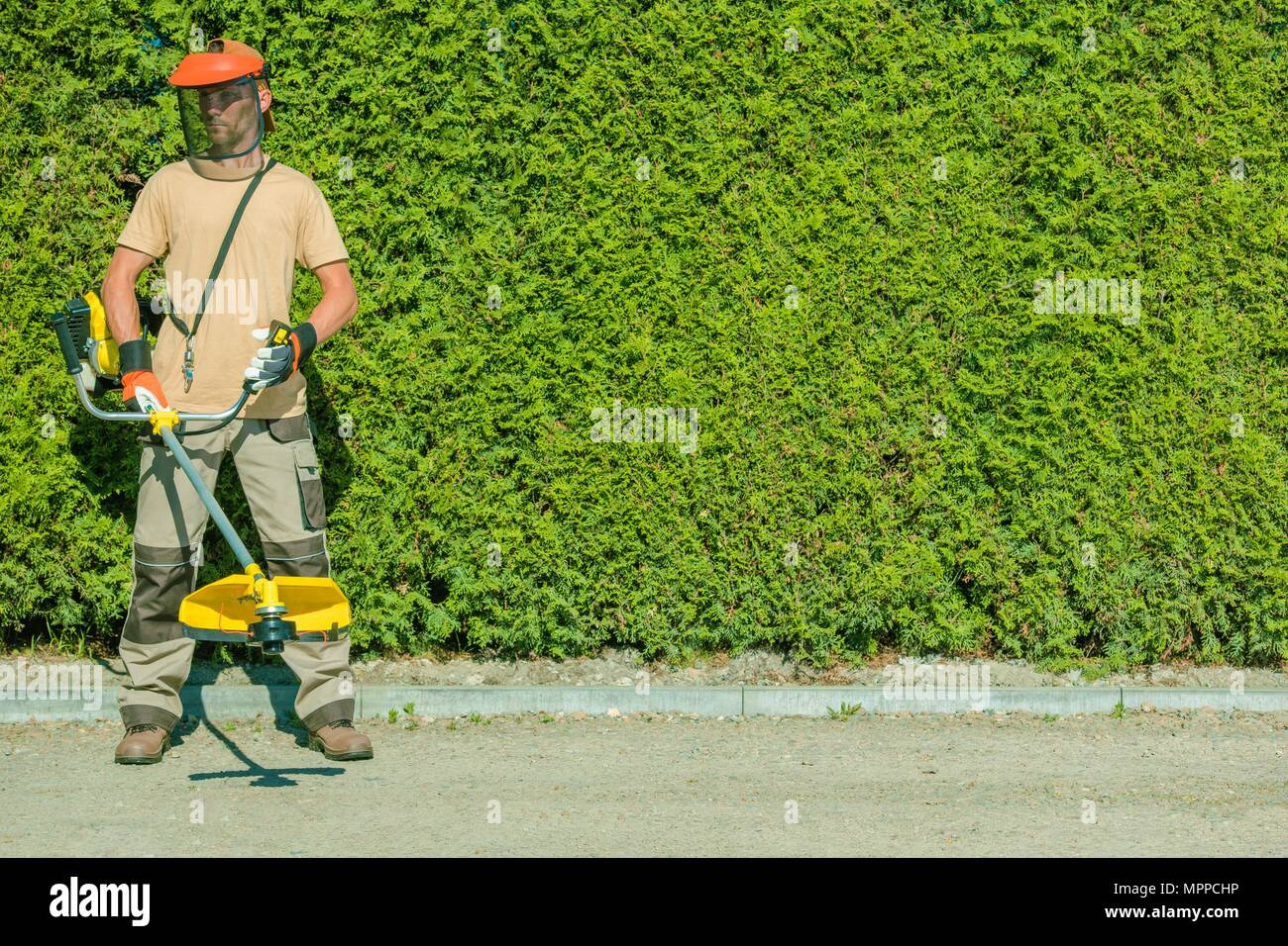 Gas String Trimmers Work. Caucasian Garden Worker with Power Tool. - Stock Image