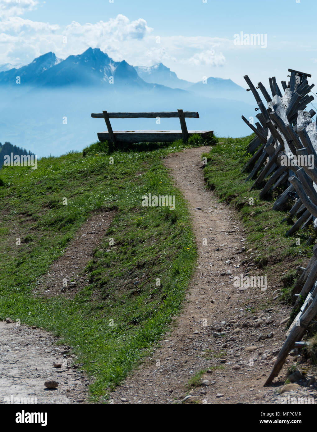 Wooden bench on mount rigi facing mount pilatus lead to by a dirt path with a wooden barricade fence next to it - Stock Image