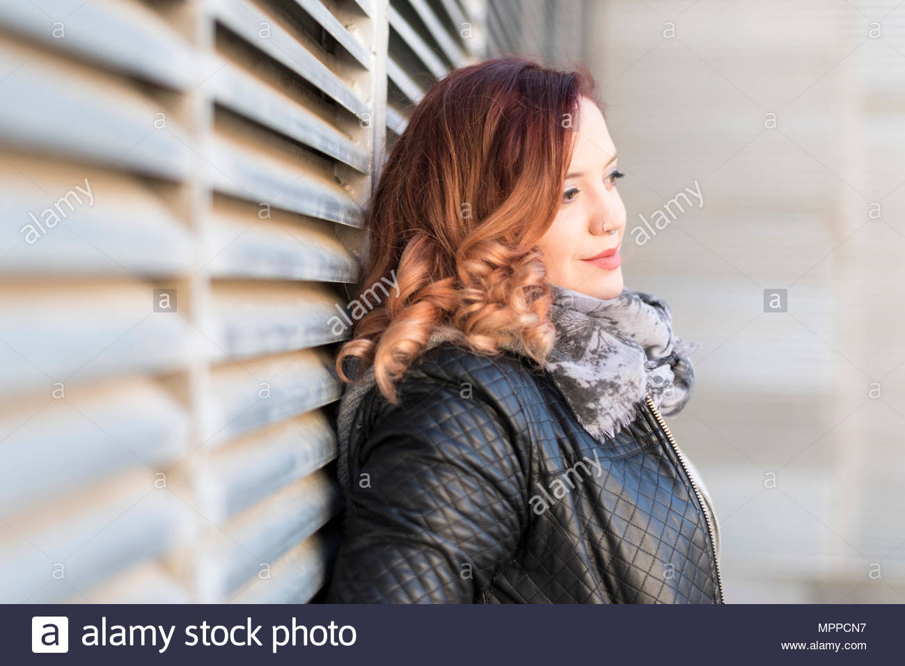 Daydreaming woman with curly hair and nose piercing - Stock Image