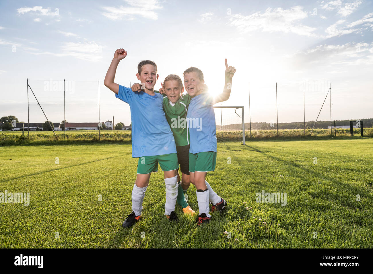Young football players cheering on football ground - Stock Image
