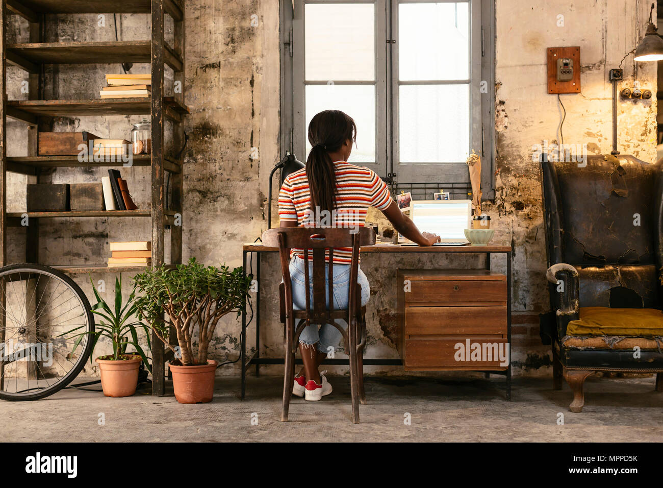 Back view of young woman sitting at desk in a loft working on laptop - Stock Image