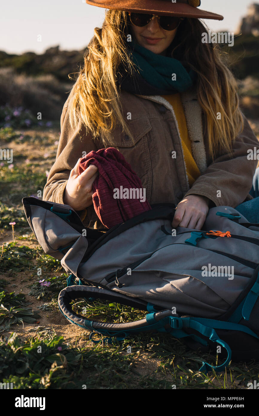 Italy, Sardinia, woman on a hiking trip having a break taking something out of backpack - Stock Image