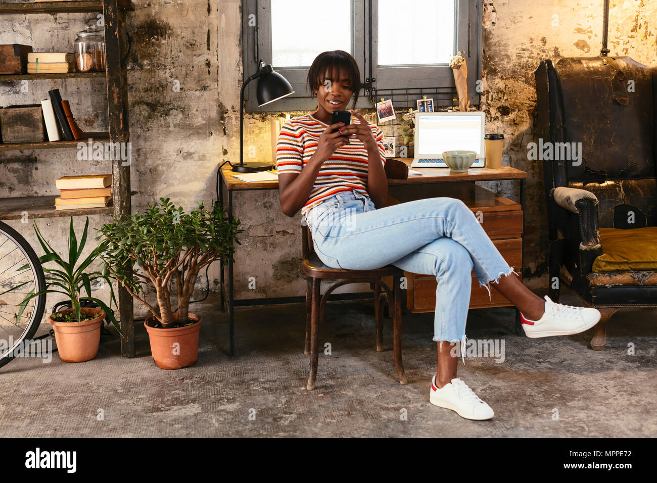Young woman sitting in front of a desk in a loft using cell phone - Stock Image