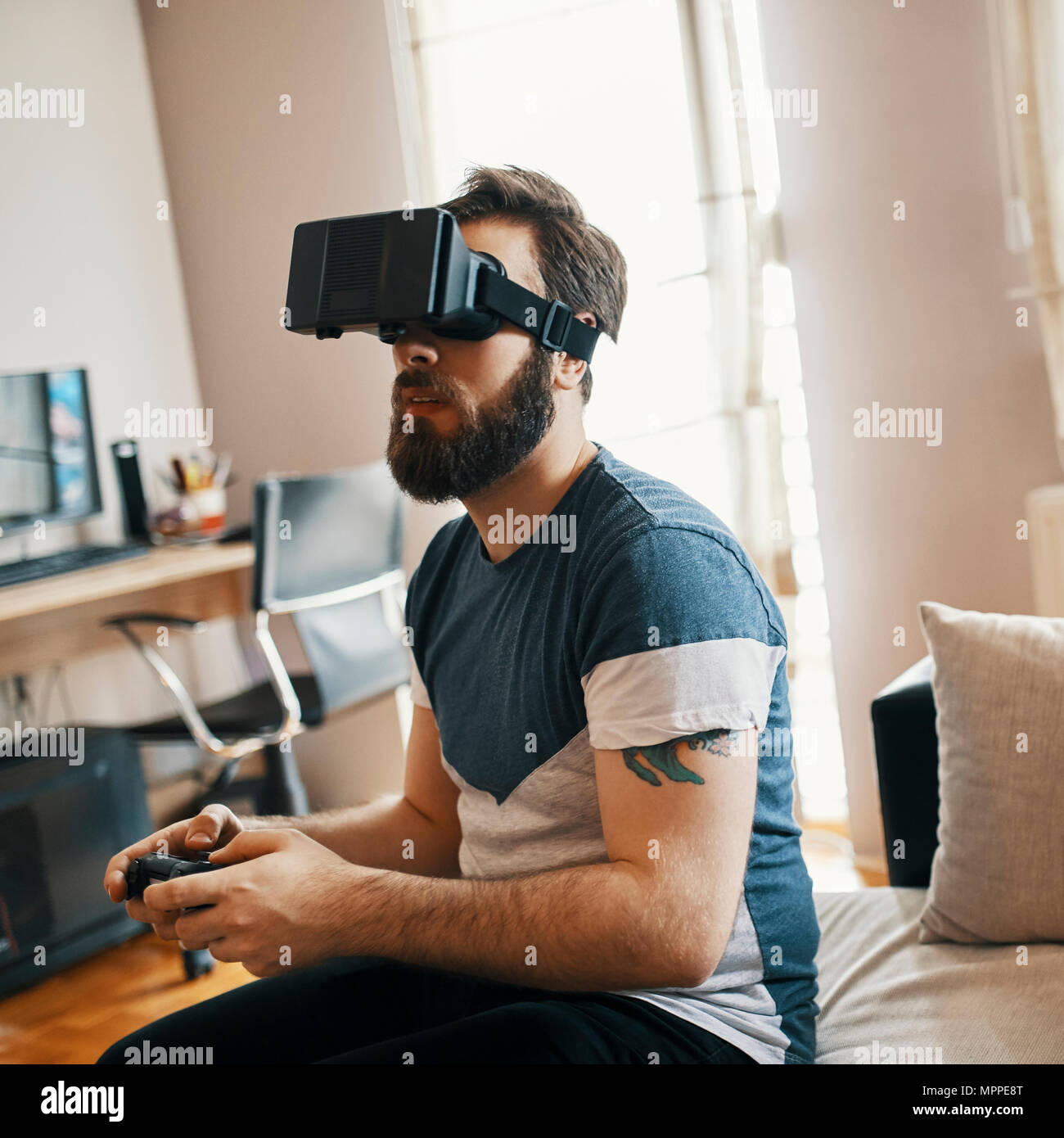 Man wearing virtual reality glasses at home playing computer game - Stock Image