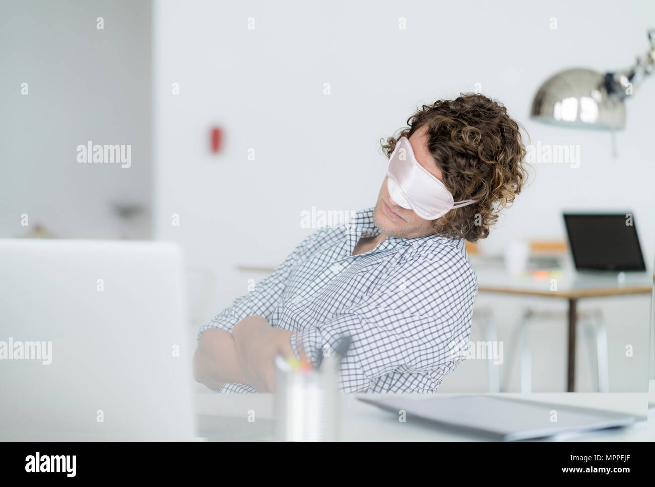 Overworked businessman sleeping at his desk wearing a sleeping mask - Stock Image
