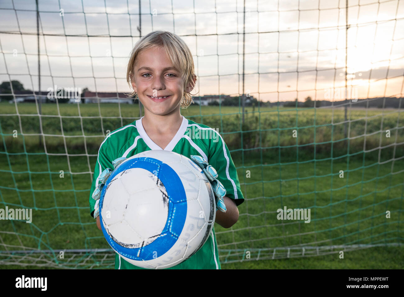 Portrait of smiling young football goalkeeper holding ball on football ground - Stock Image