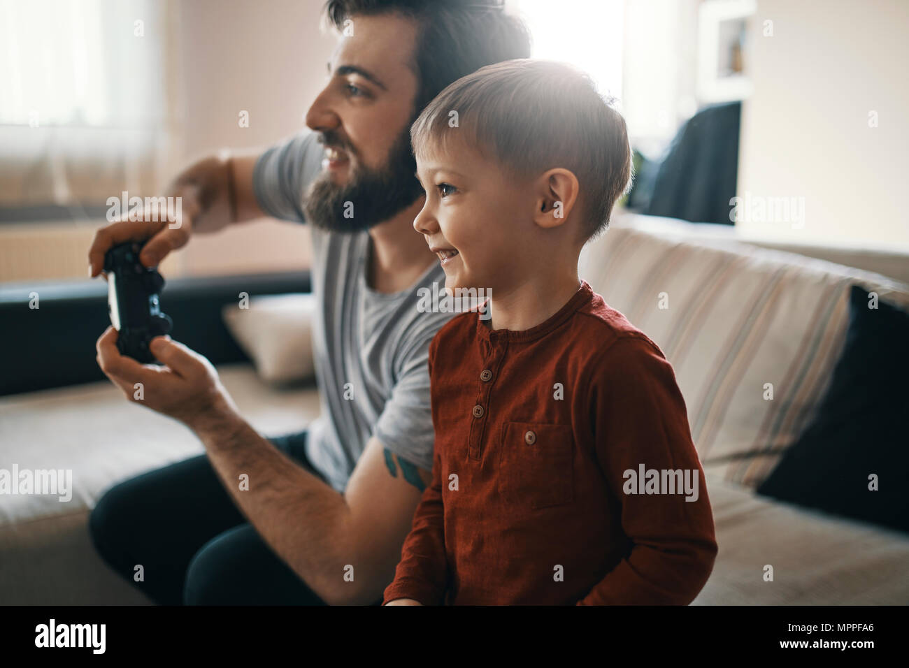 Happy little boy playing computer game with his father at home - Stock Image