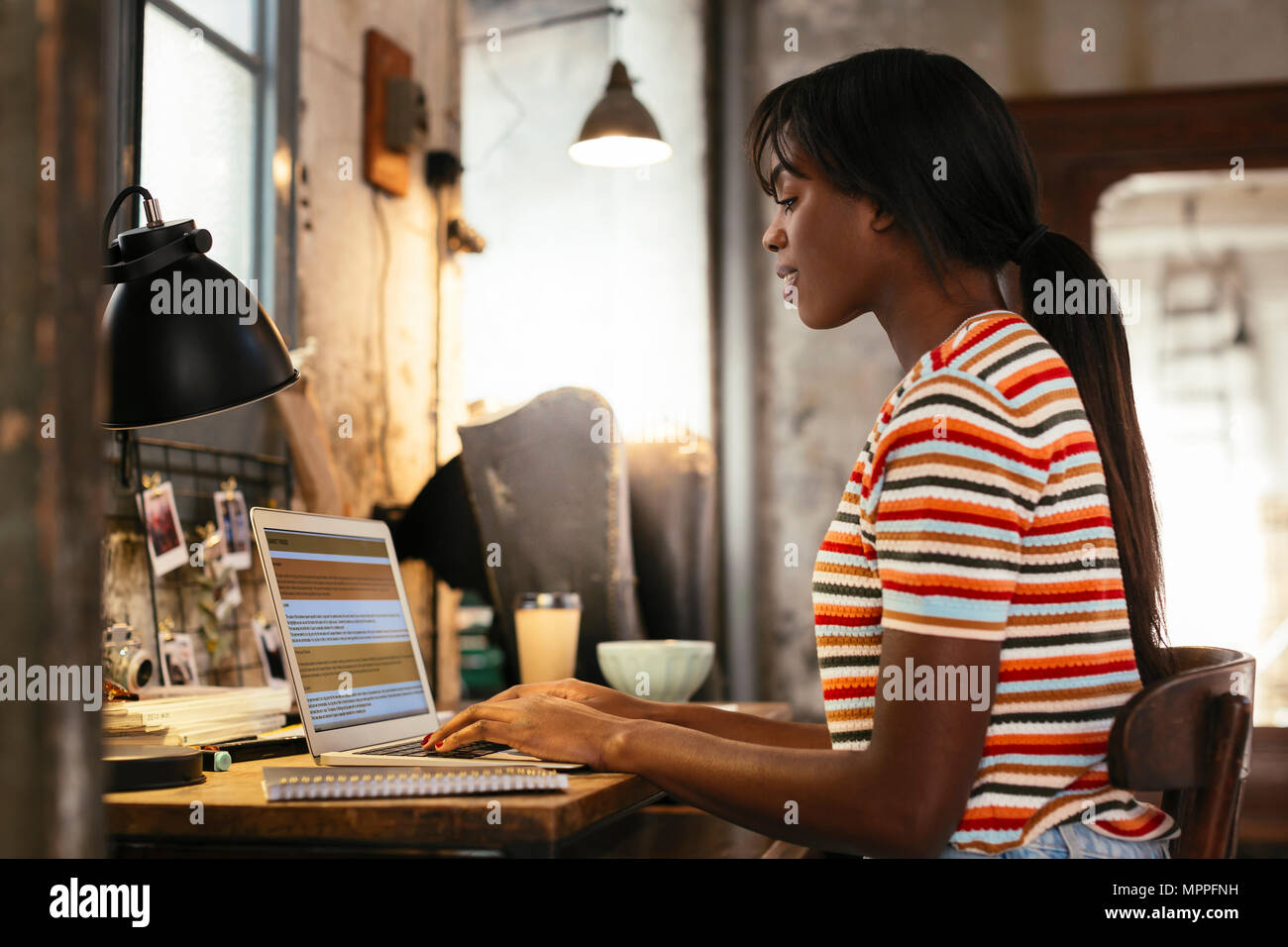 Young woman sitting at desk in a loft working on laptop - Stock Image