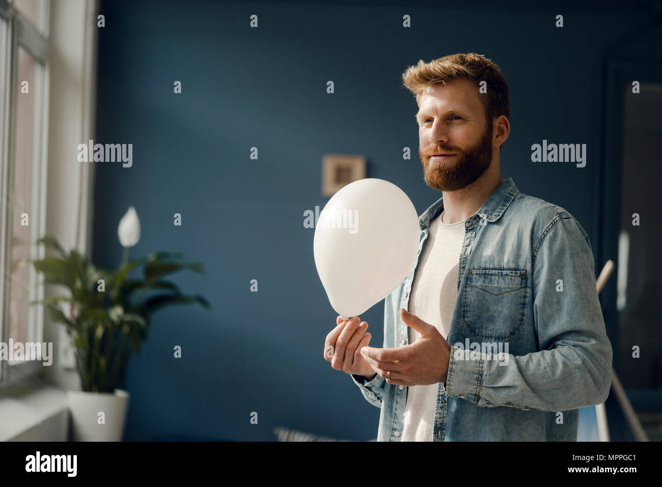 Man holding a balloon, smiling - Stock Image