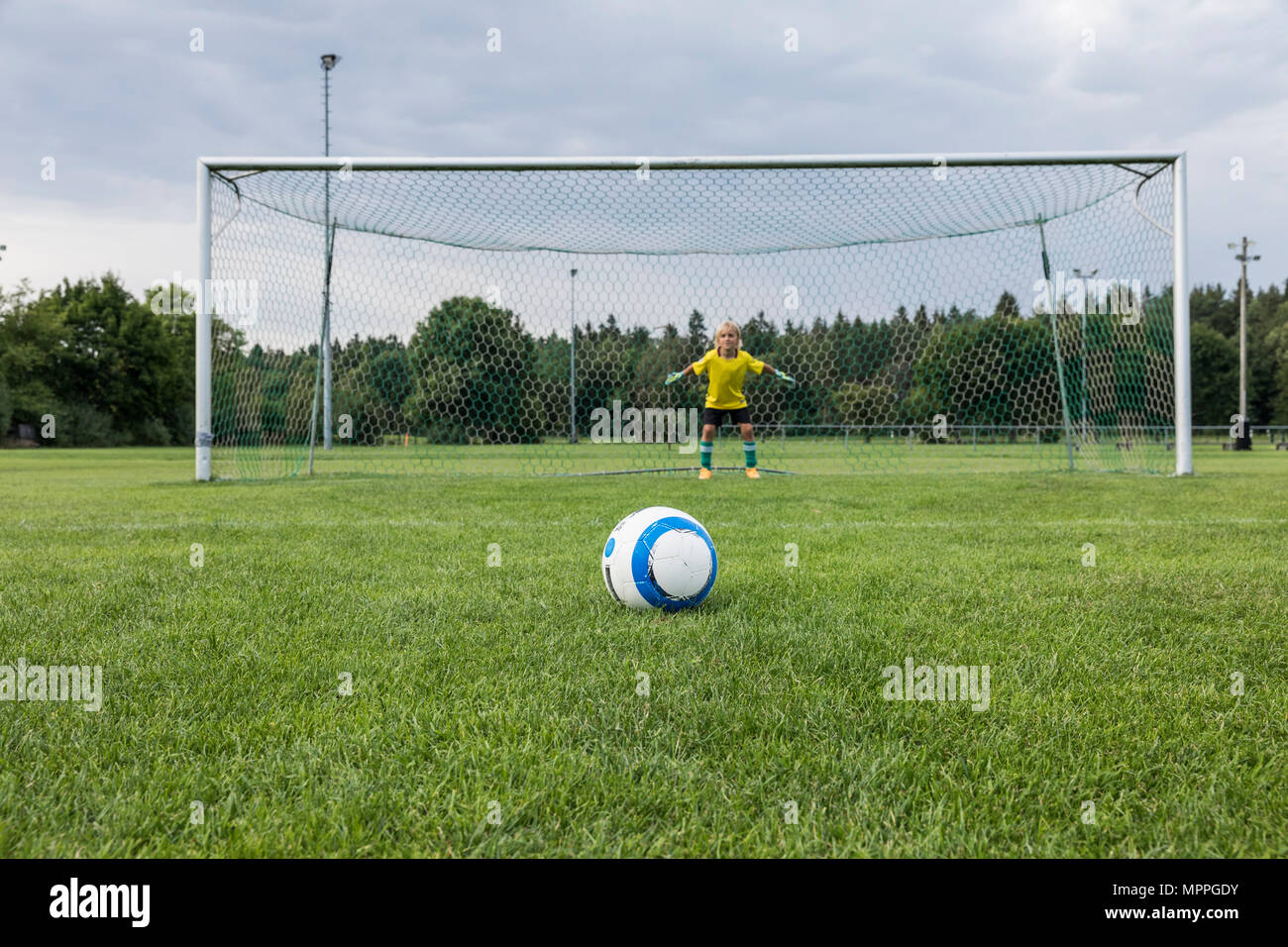 Young football goalkeeper with ball on football ground - Stock Image