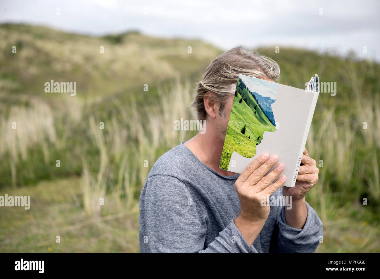 Man reading story book in the dunes, covering his face - Stock Image