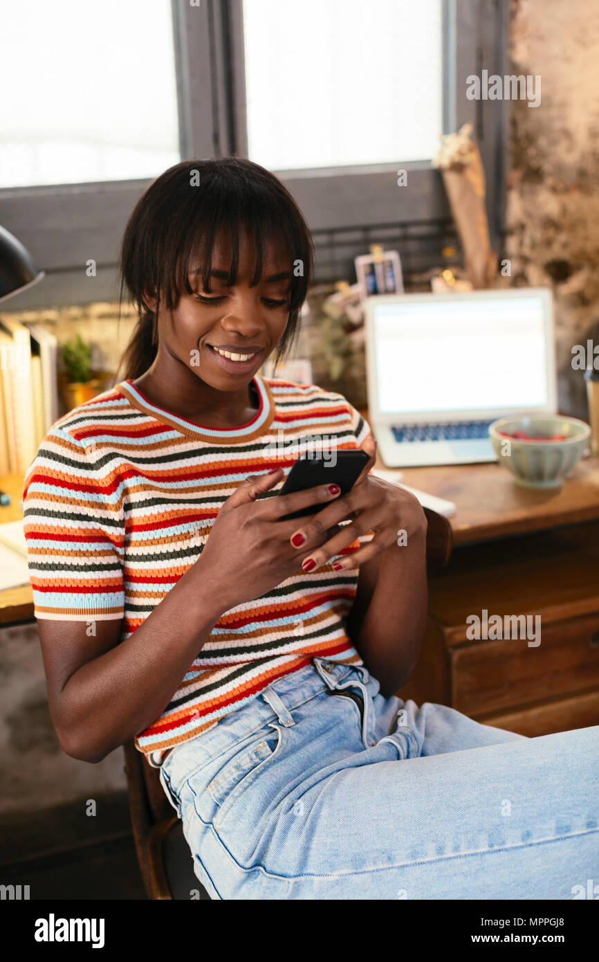 Portrait of smiling young woman sitting in front of desk in a loft using cell phone - Stock Image