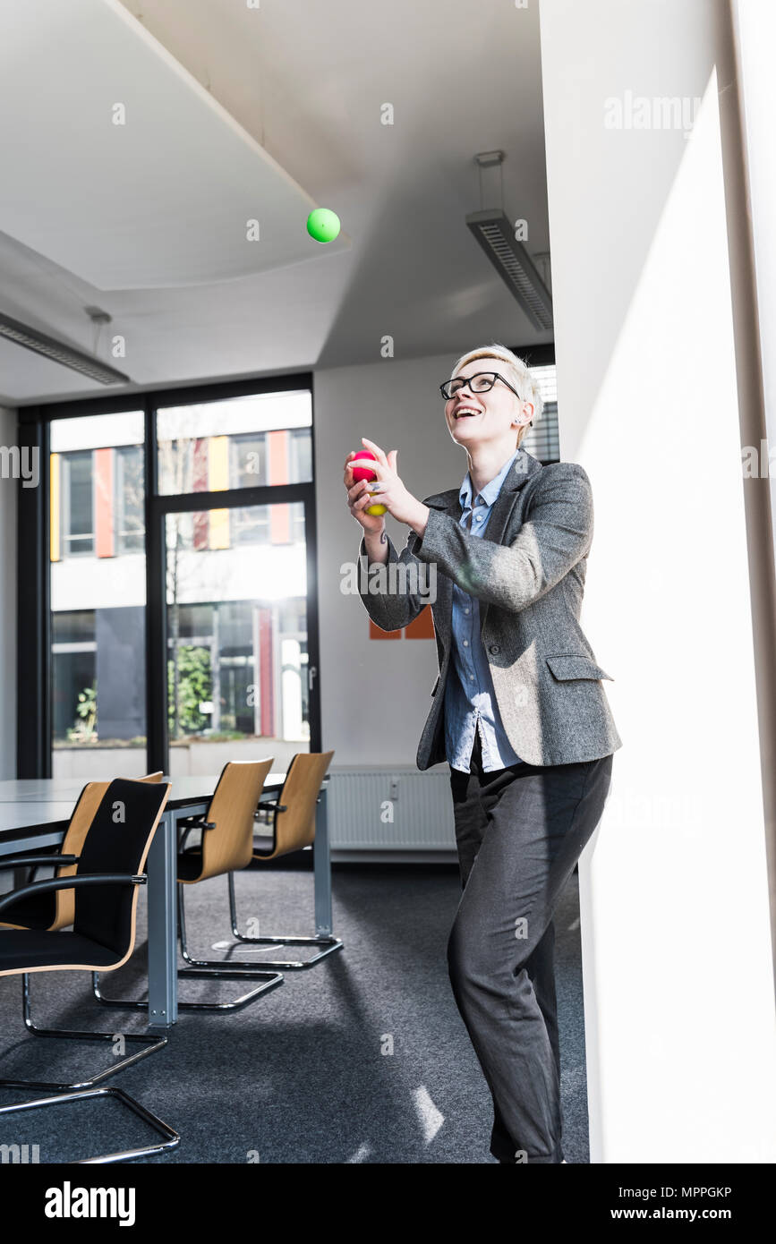 Laughing businesswoman juggling with balls in office - Stock Image