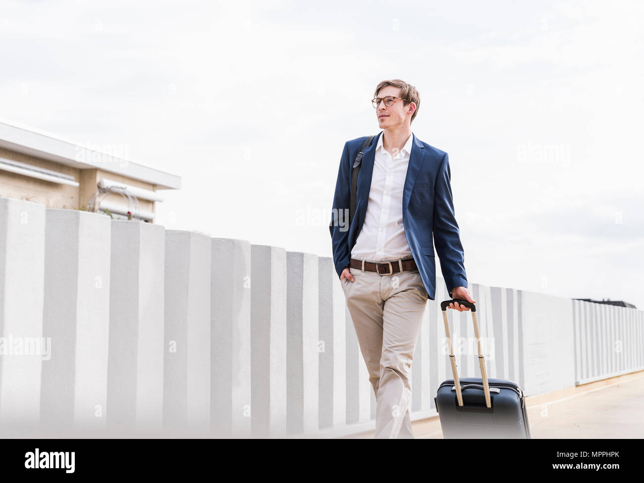 Confident businessman with rolling suitcase walking at parking garage - Stock Image