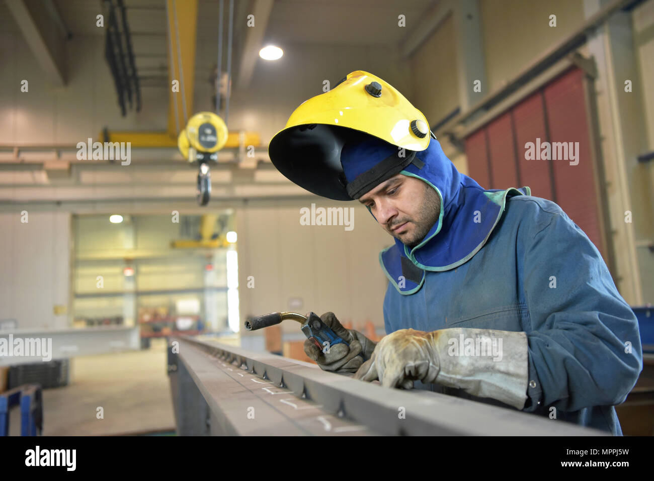 Welder checking metal surface in factory - Stock Image