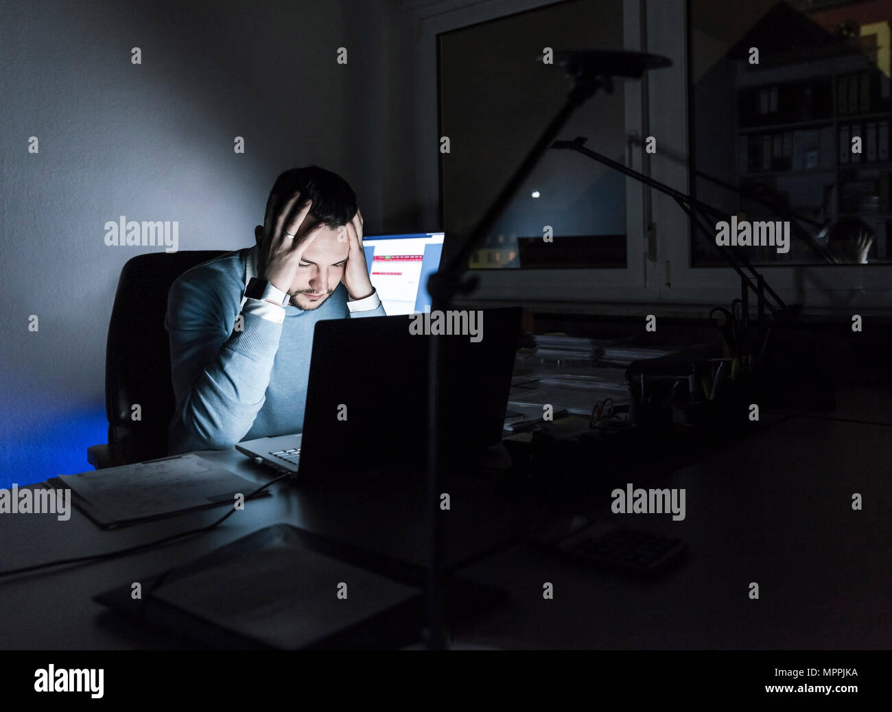 Tired businessman sitting at desk in office at night - Stock Image