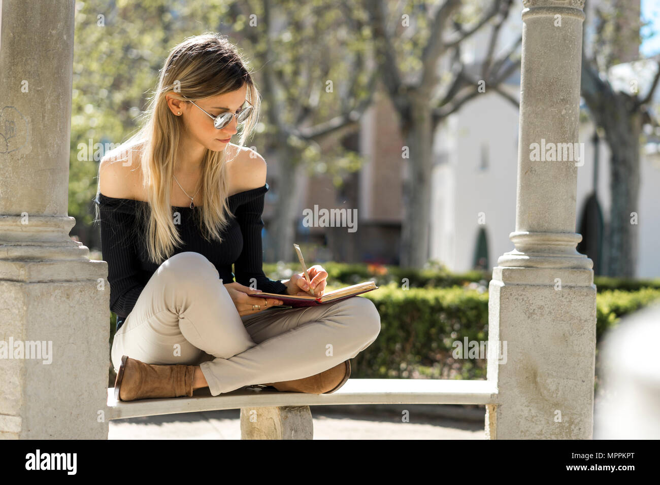 Young woman with notebook sitting on bench writing down something - Stock Image
