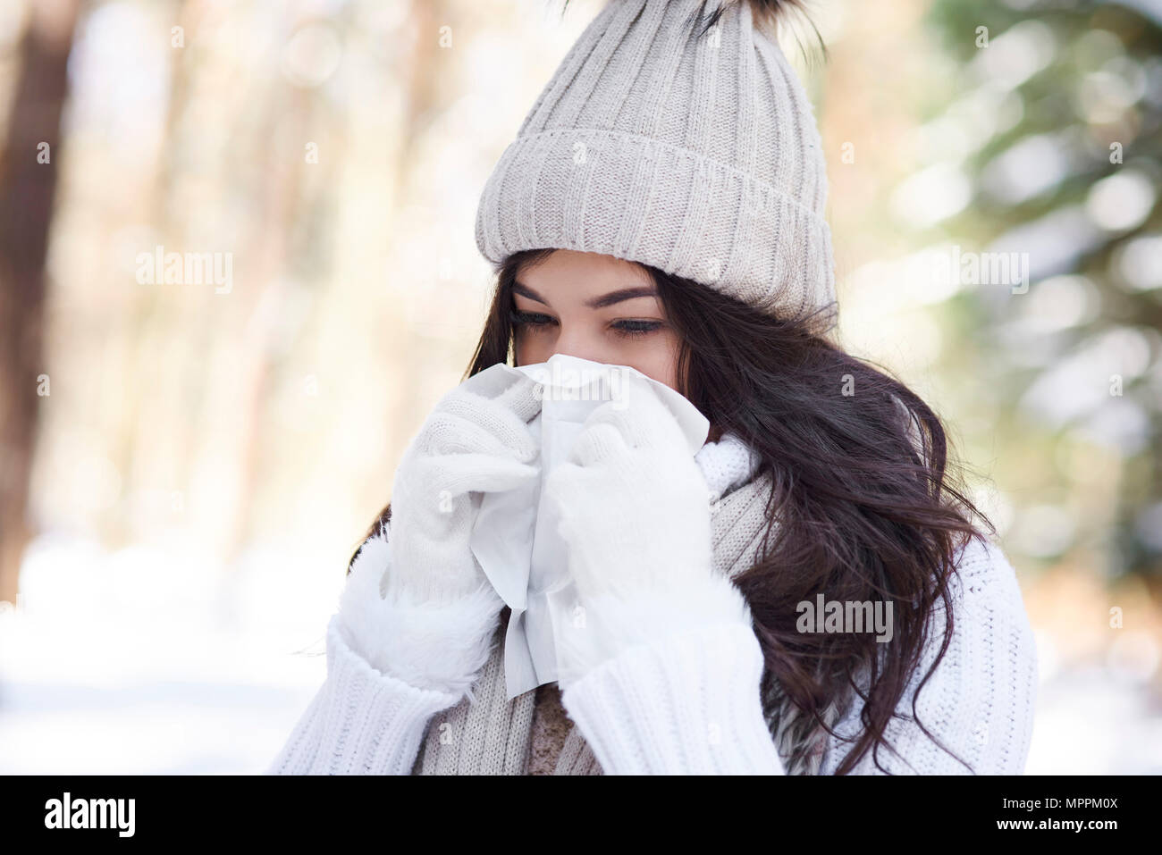 Young woman blowing nose in winter - Stock Image