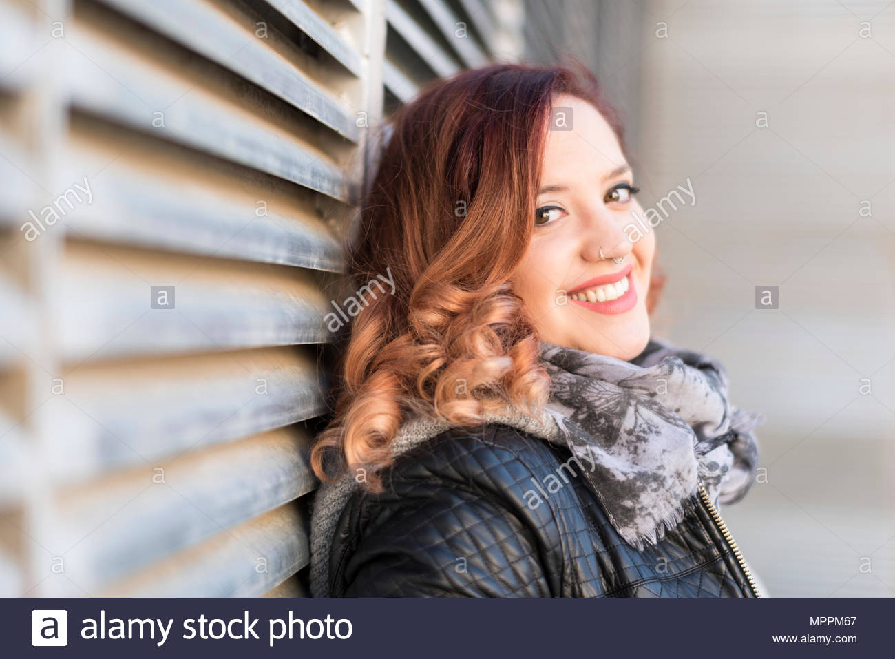 Portrait of happy young woman with curly hair and nose piercing - Stock Image