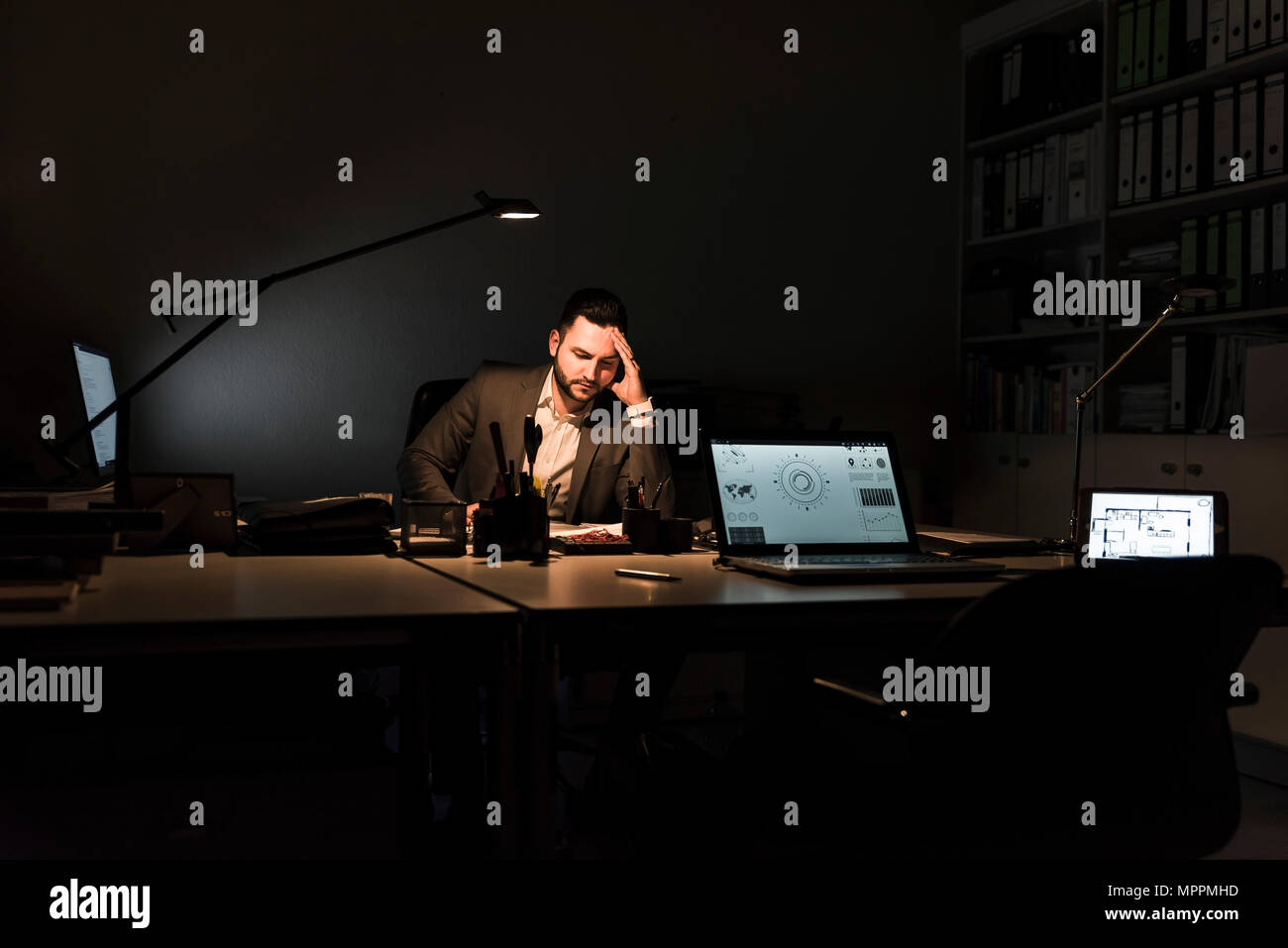Businessman working in office at night - Stock Image