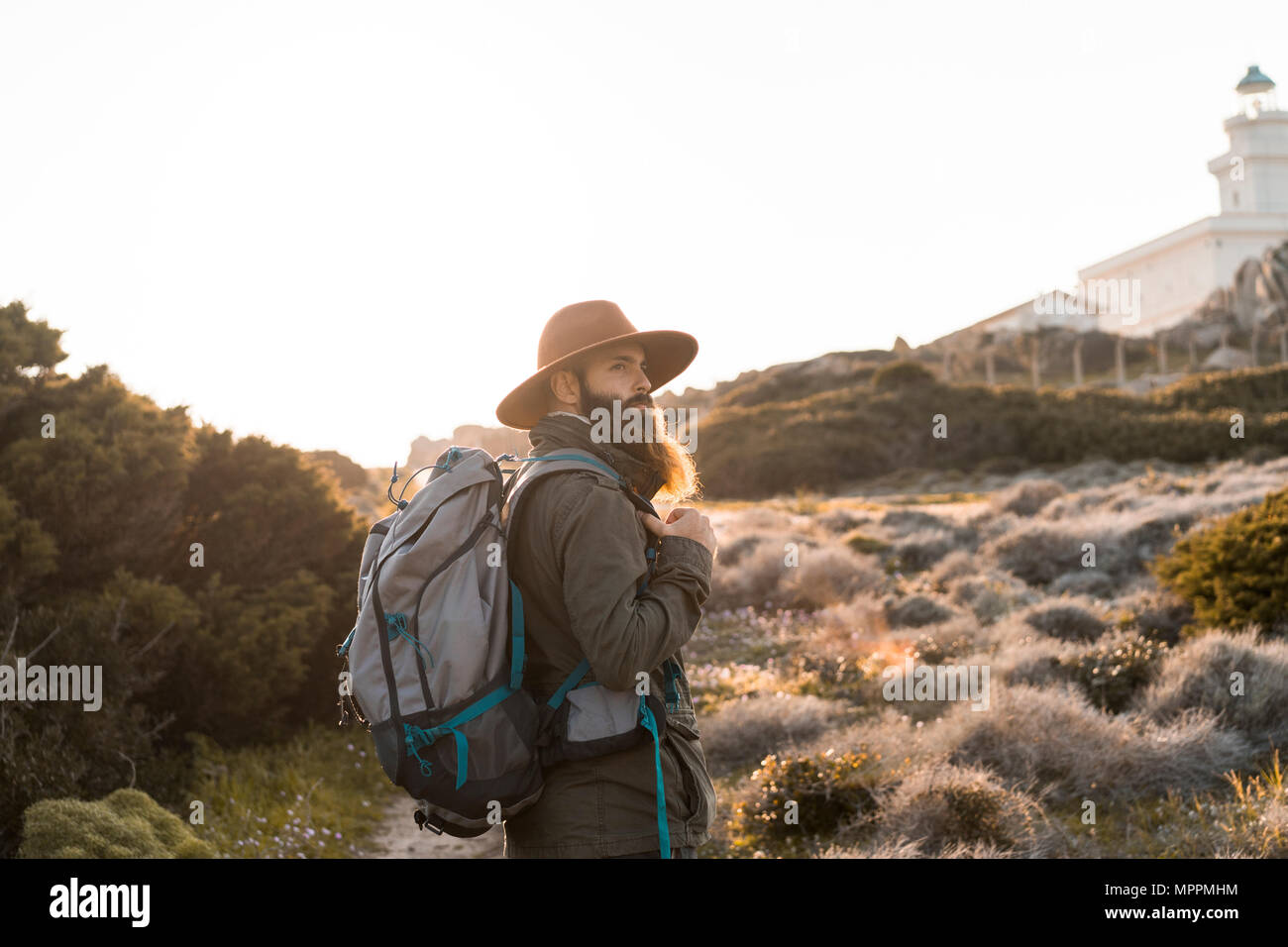 Italy, Sardinia, hiker with hat and backpack watching something - Stock Image