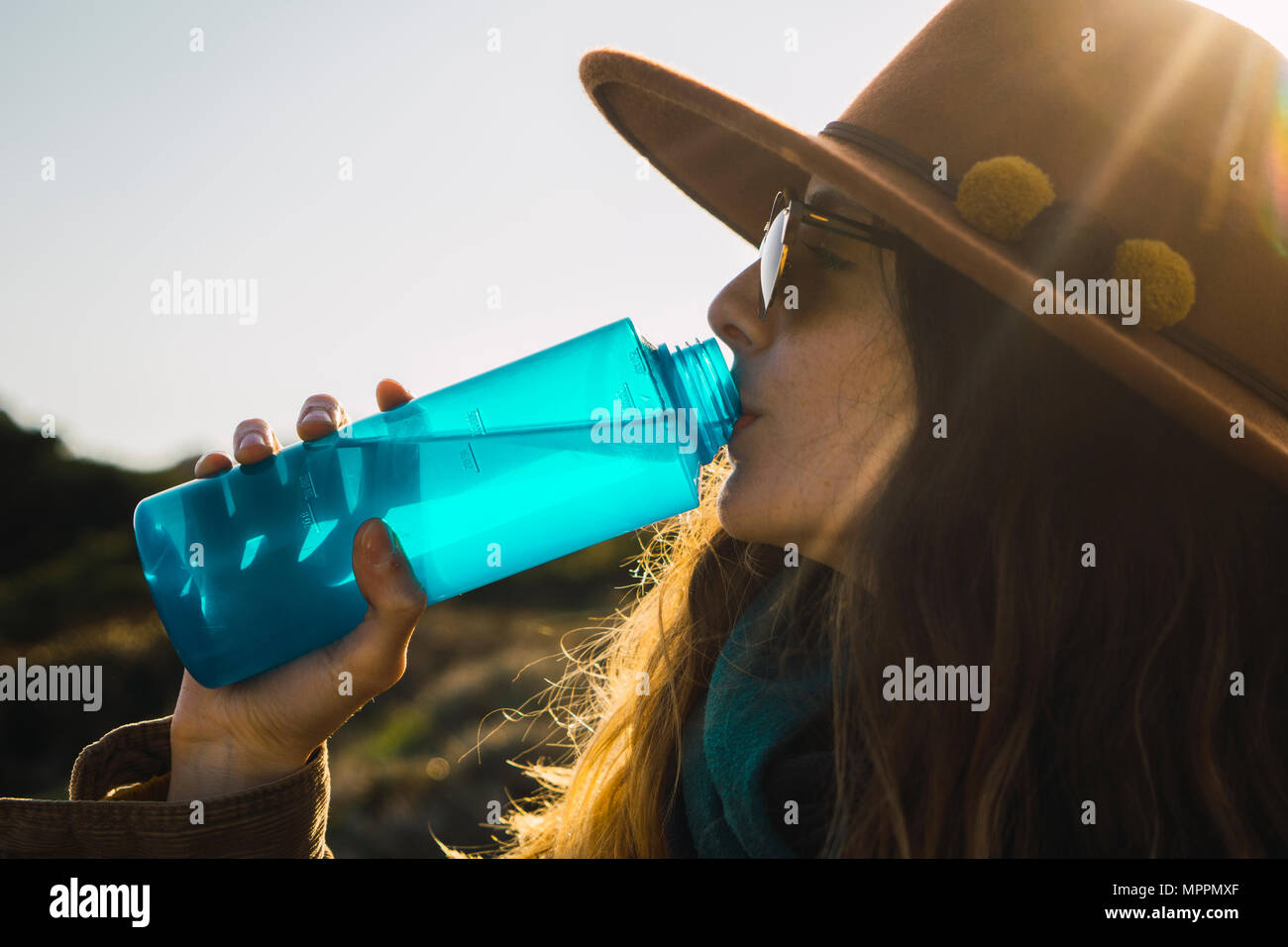 Woman on a hiking trip drinking from water bottle - Stock Image