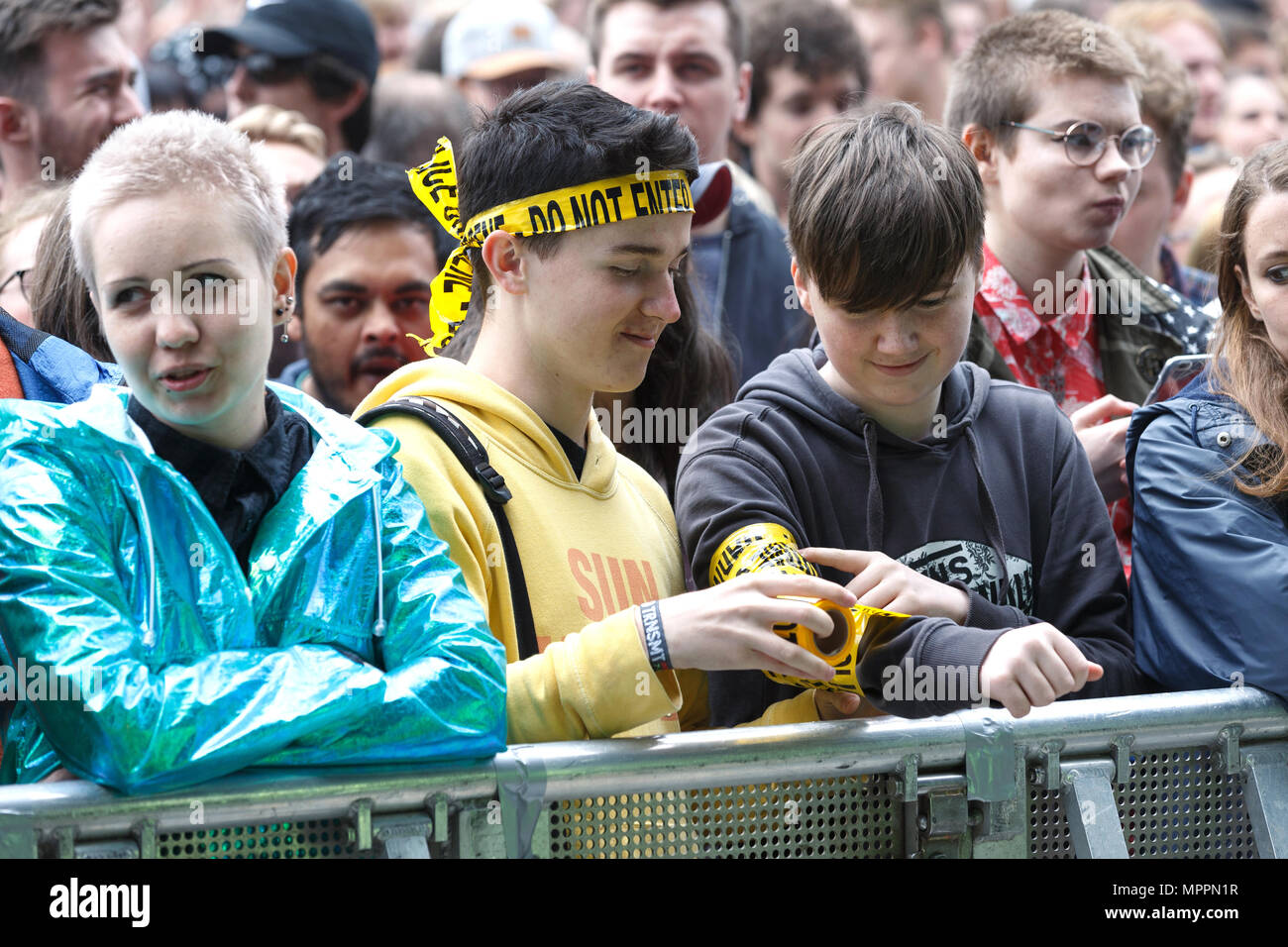 Teenage boys in the front row at a music festival. One is wrapping the other's arm in 'do not enter' novelty tape. - Stock Image