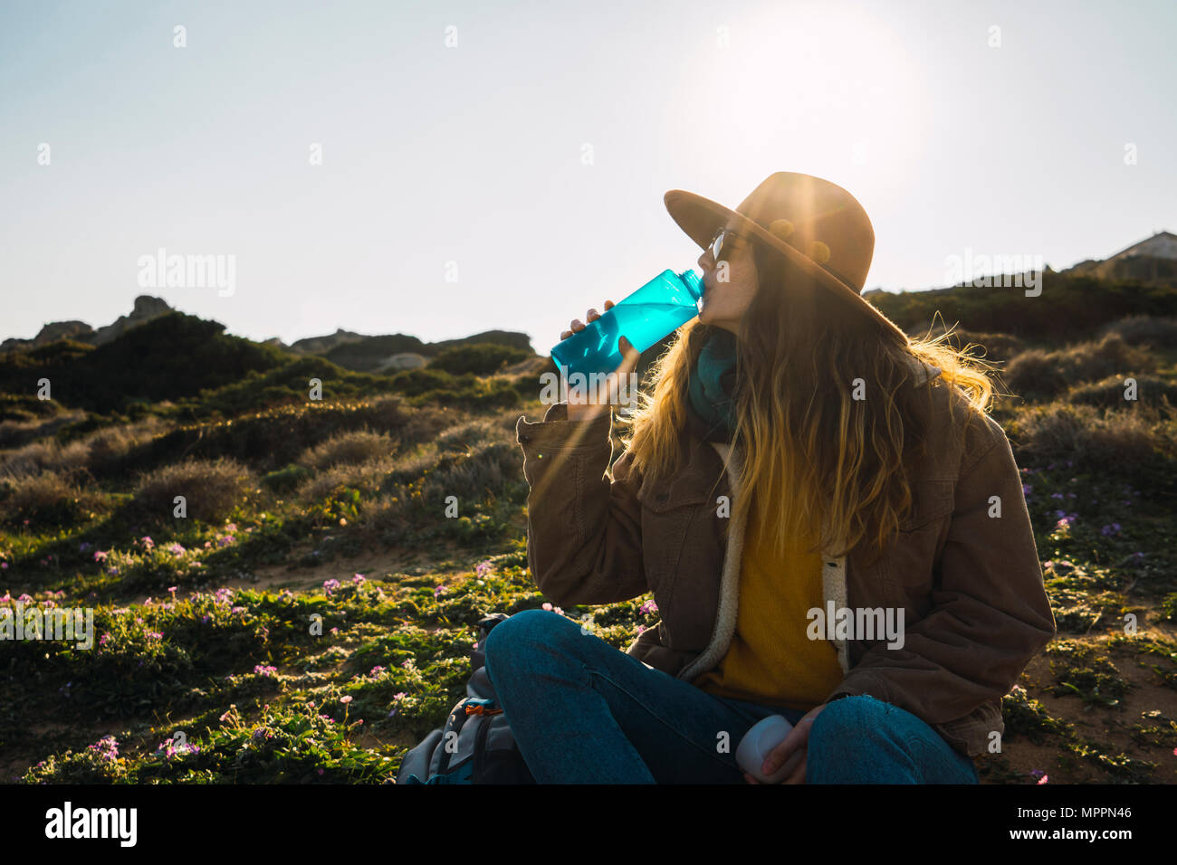 Italy, Sardinia, woman on a hiking trip having a break drinking from water bottle - Stock Image