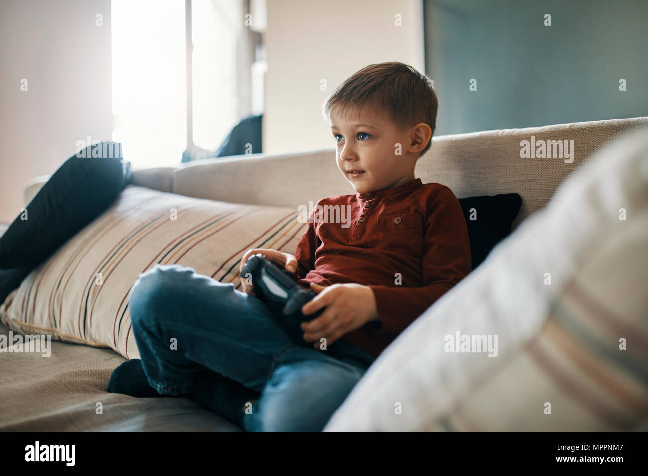 Portrait of little boy sitting on the couch playing computer game - Stock Image