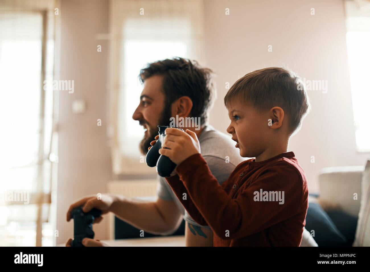 Little boy playing computer game with his father at home - Stock Image