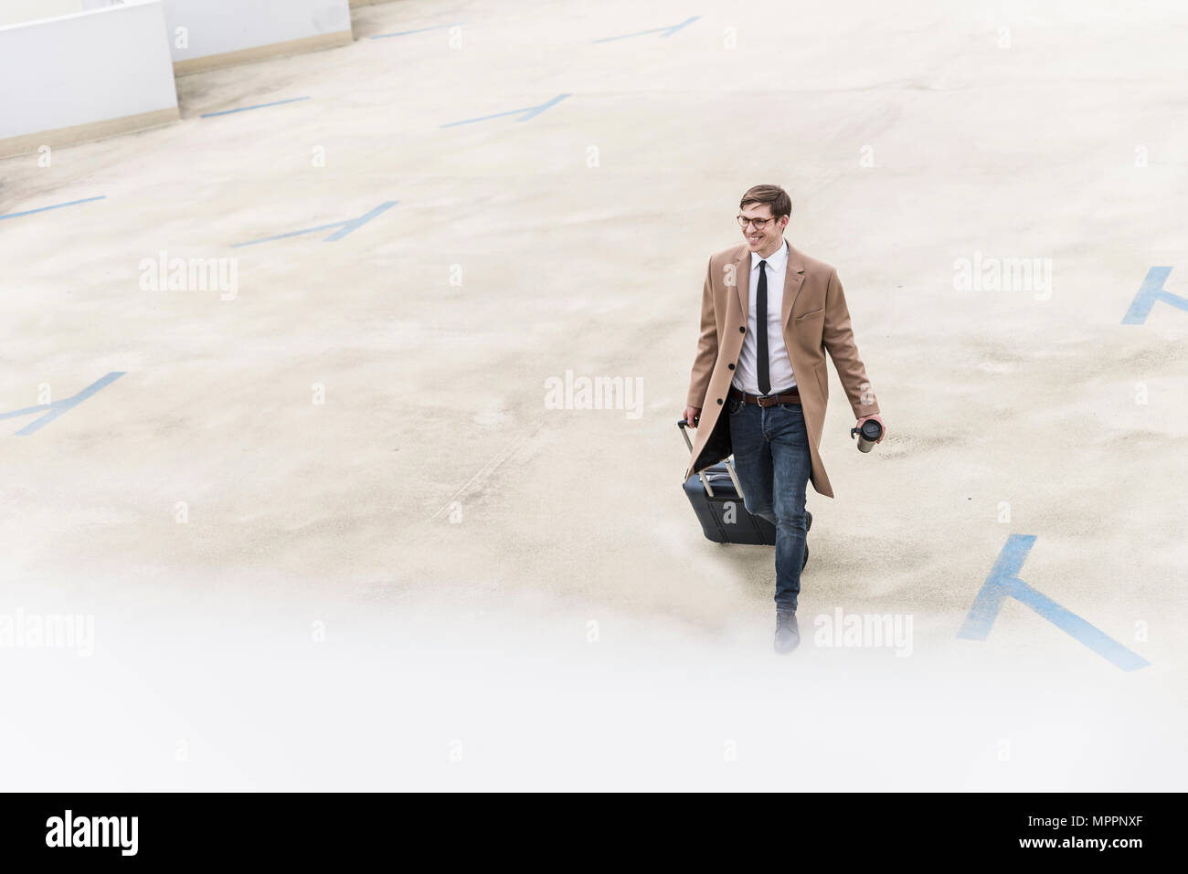 Smiling businessman with rolling suitcase walking at parking garage - Stock Image