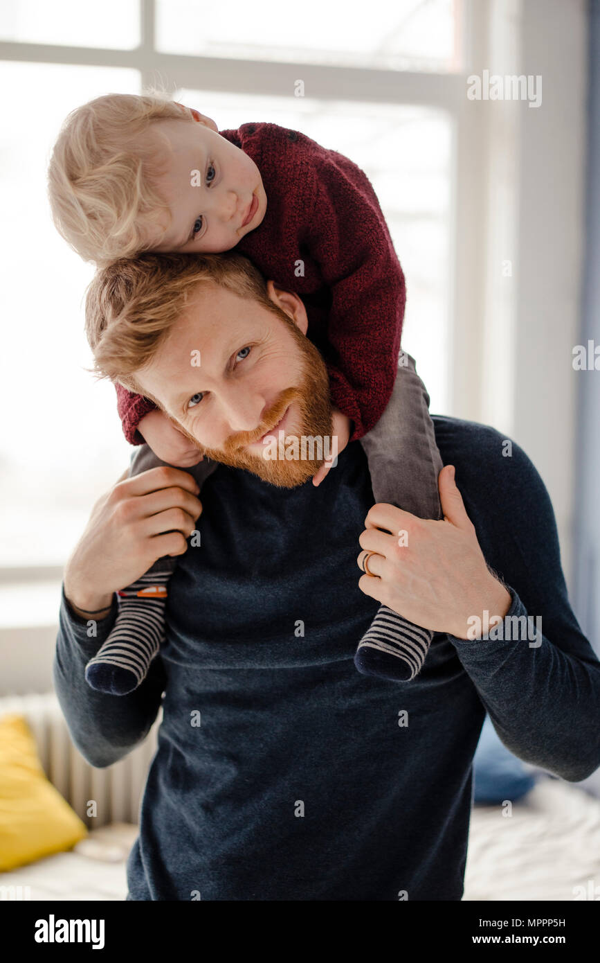 Father and baby son having fun together at home - Stock Image