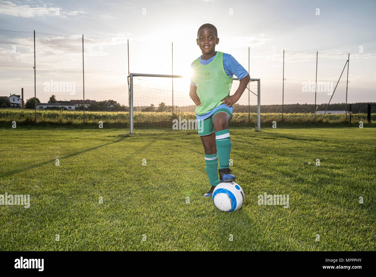 Portrait of confident young football player with ball on football ground - Stock Image