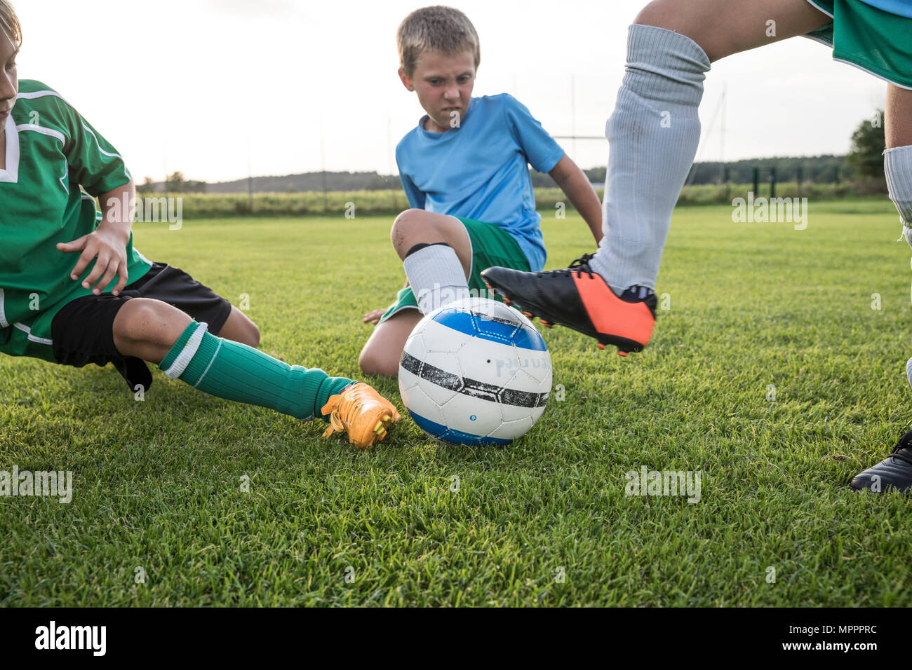 Young football players tackling on football ground - Stock Image