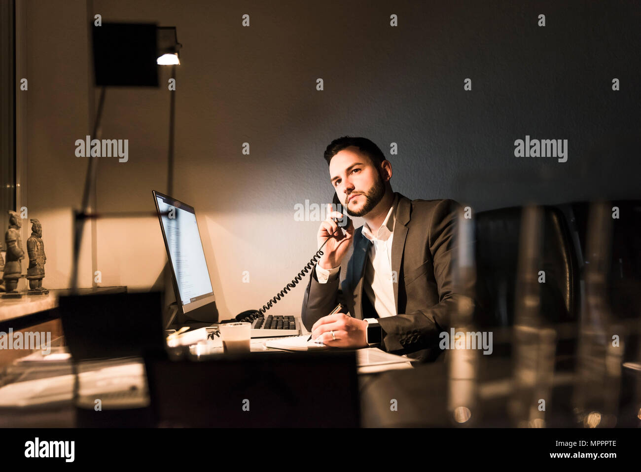 Businessman on the phone in office at night - Stock Image