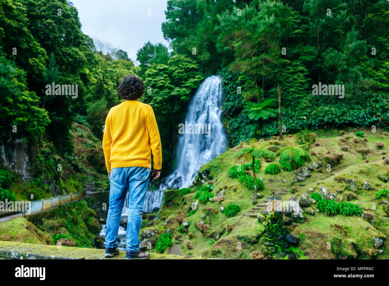 Azores, Sao Miguel, rear view of man looking at a waterfall in the Ribeira dos Caldeiroes Natural Park - Stock Image