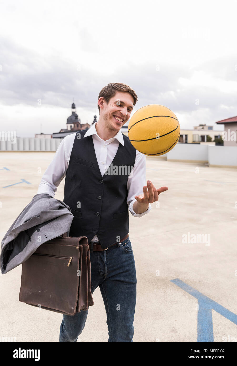 Happy businessman with basketball walking at parking garage - Stock Image