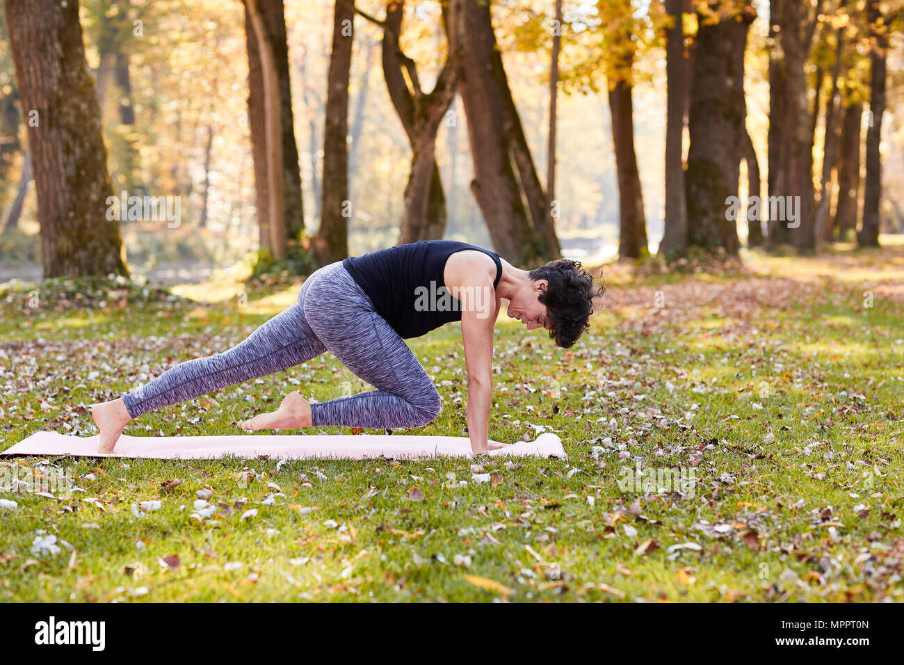 Mid adult woman in forest practicing yoga, climber exercise - Stock Image