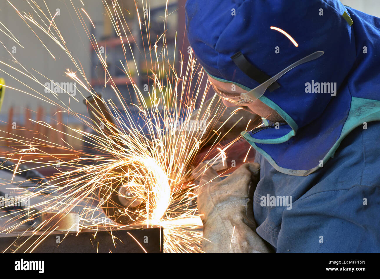 Worker using angle grinder in factory - Stock Image