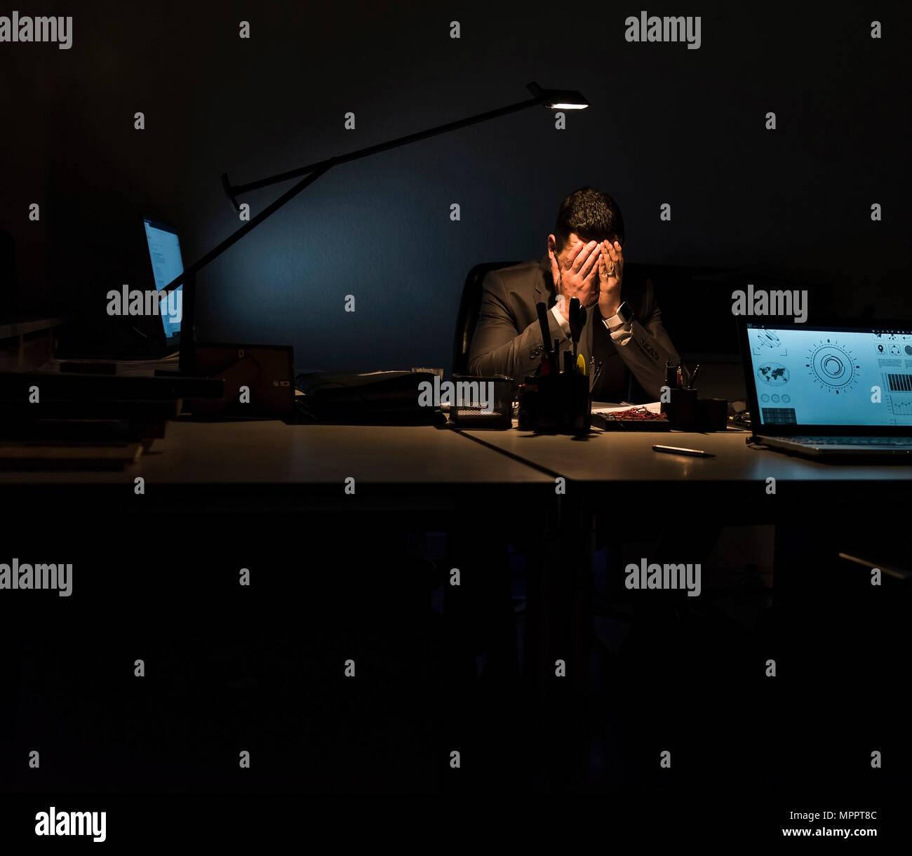 Overstressed businessman sitting at his desk in the dark - Stock Image
