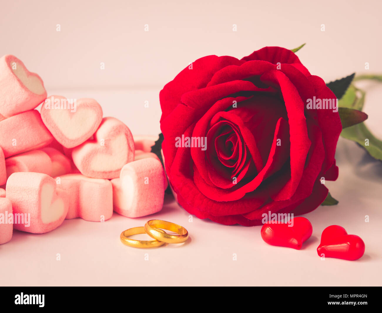 Romantic Red Rose With Golden Rings And Red Hearts On