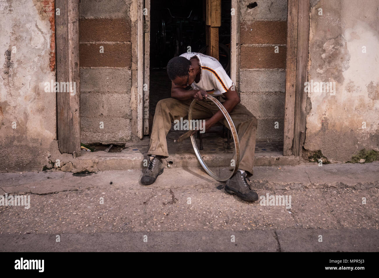 Adult male cleaning and brushing inside a metal bicycle wheel, Havana Cuba - Stock Image