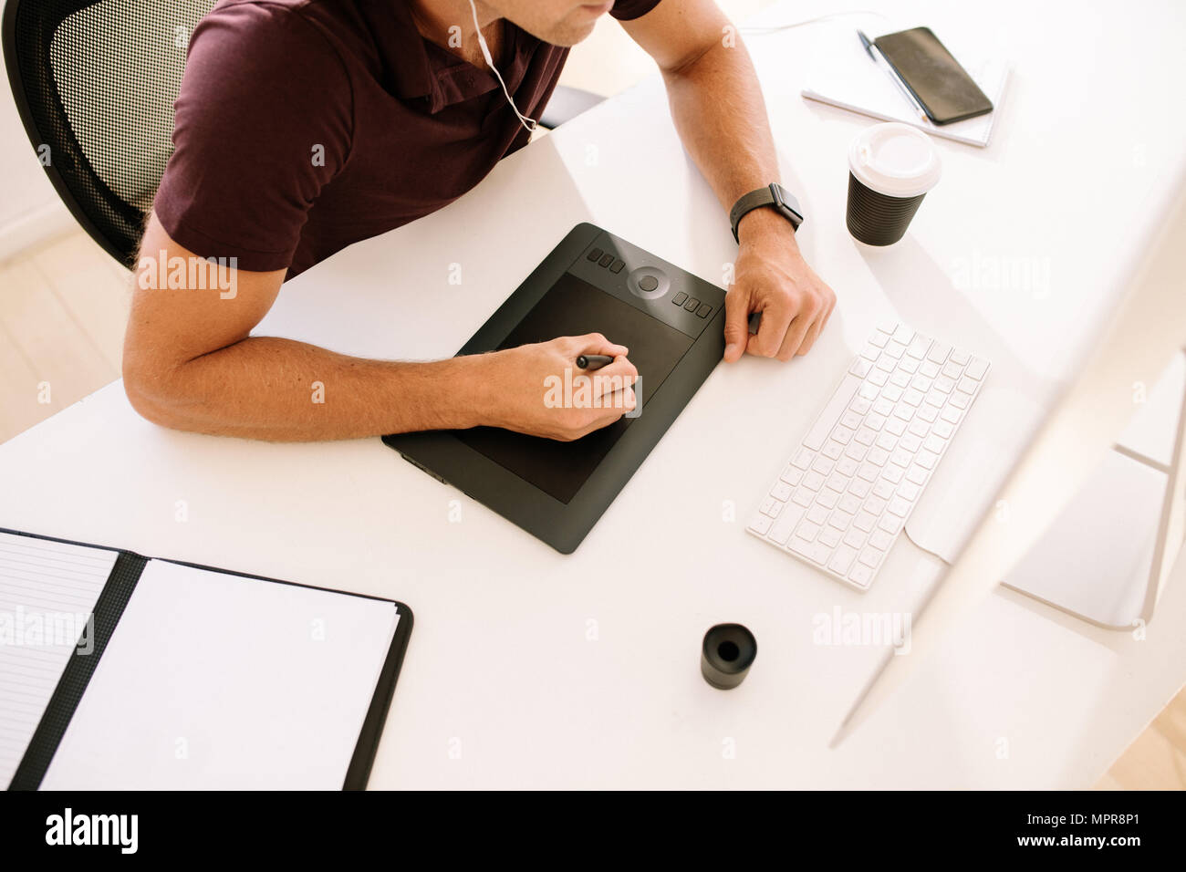 Businessman working on computer and using a digitizer to make notes. Man listening to audio while working on computer with a coffee glass on the table - Stock Image