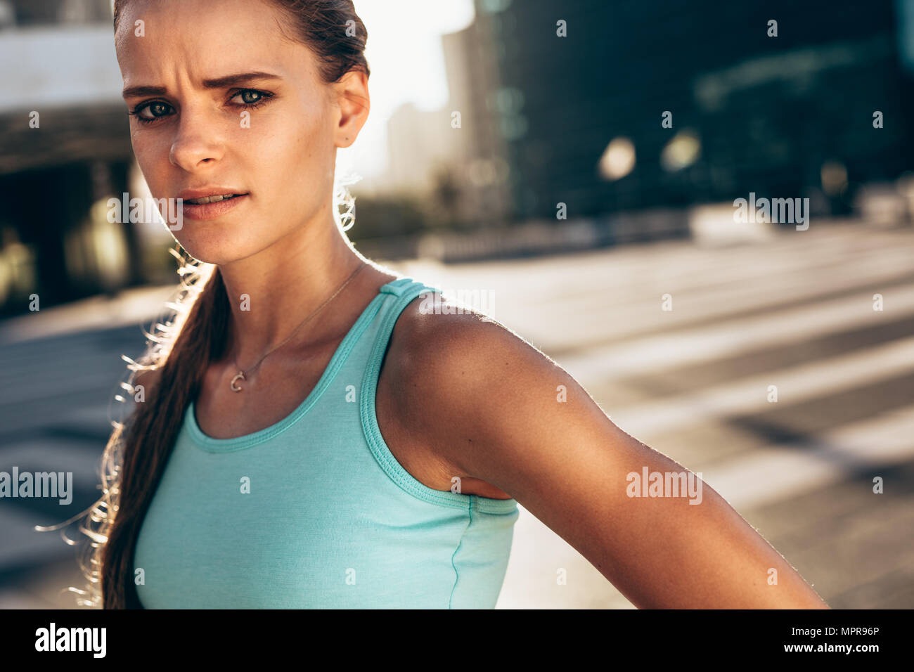 Strong woman in sports bra standing outdoors and standing at camera. Sportswoman looking with serious expressions after working out in morning outdoor Stock Photo