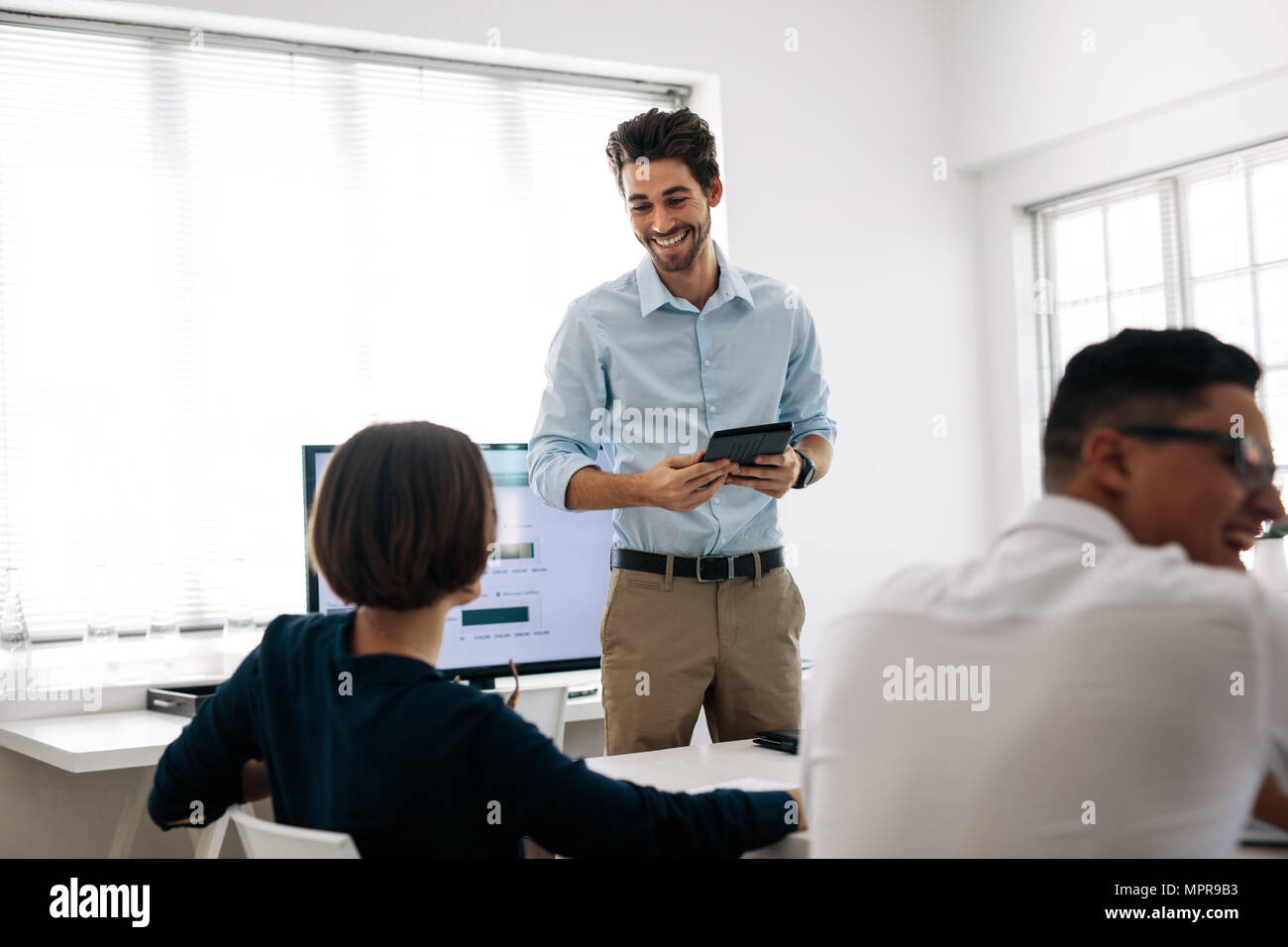 Businessman making a presentation to his colleagues in office. Office colleagues sharing lighter moments sitting at the conference room. - Stock Image
