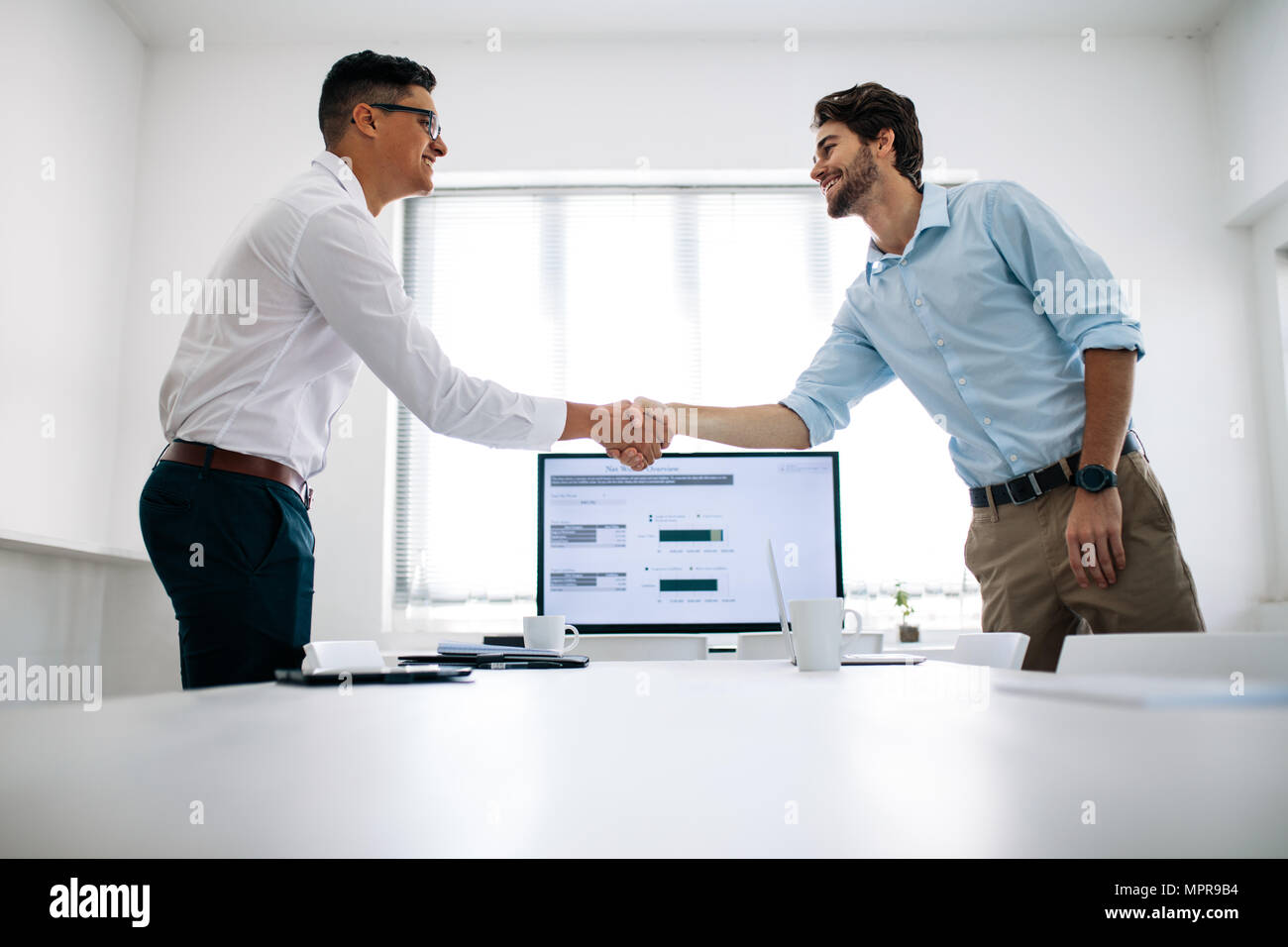 Business colleagues shaking hands in the conference table. Happy businessmen greeting each other in the meeting room. - Stock Image